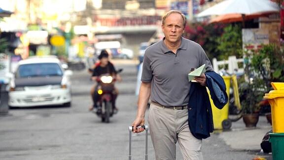 Um das Erbe seines Vaters anzutreten, reist Holger (Ulrich Tukur) nach Thailand.