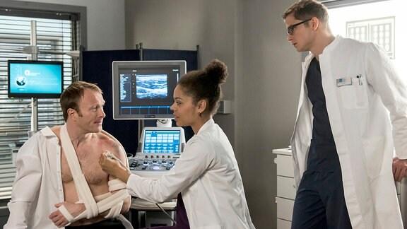 Nach dem Einrenken untersuchen die Ärzte Bernd Müllers Schulter per Ultraschall - und machen eine unschöne Entdeckung. V.l.n.r. Bernd Müller (Merten Schroedter), Vivienne Kling (Jane Chirwa), Elias Bähr (Stefan Ruppe)