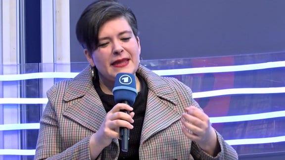 Eine Frau spricht in eine Mikrofon.