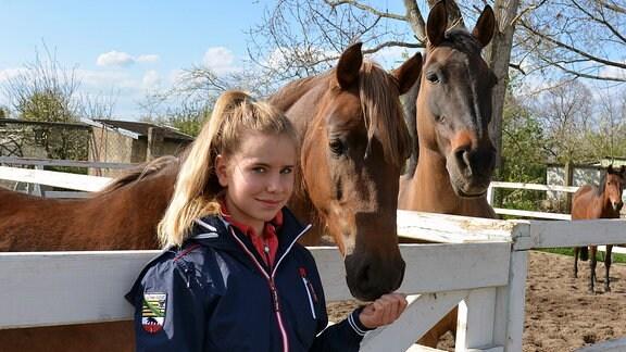 Mädchen und zwei Pferde auf der Koppel