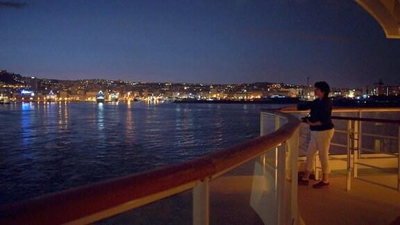 Eine Frau mittleren Alters steht an der Glasreling eines Schiffes und schaut auf eine nächtliche Stadt. Die Lichter eben dieser sieht man im Hintergrund auf dem Wasser.