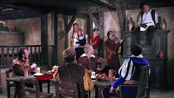 Prinz Störenfried (Gerhard Rachold, vorne rechts, Rückenansicht) und seine Ritterbande schikanieren den armen Wirt (Fritz Schlegel, hinten ganz rechts oben).