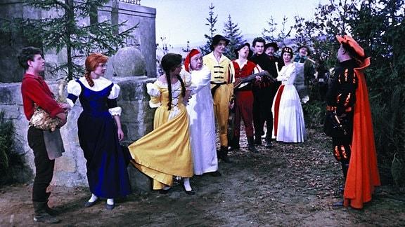 Angeführt vom Schuster Klaus (Kaspar Eichel, ganz links), den Wirtstöchtern Lies (Katharina Lind, 2.v.l.) und Gret (Renate Usko, 3.v.l.) sowie deren Vater, dem Wirt (Fritz Schlegel, 4.v.l.) und den Musikanten, erreicht die illustre Truppe das Königsschloss.