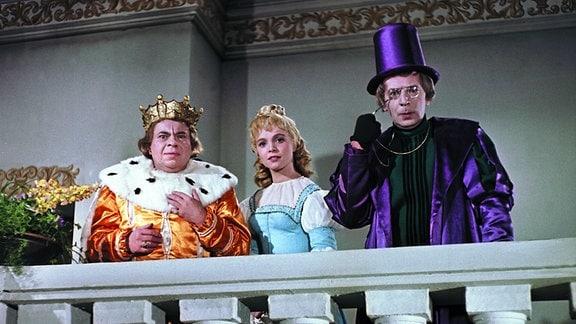 Der König (Heinz Scholz, links), die traurige Prinzessin (Karin Ugowski, Mitte) und der Hofgelehrte (Gerd E. Schäfer, rechts) beobachten die Ankunft