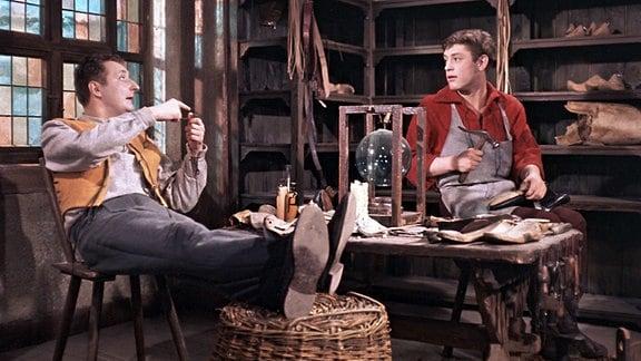 Während der Schuster Klaus (Kaspar Eichel, rechts) fleißig arbeitet, sitzt sein Bruder Franz (Peter Dommisch, links) nur faul herum.