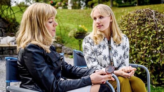 Desirée (Louisa von Spies, r.) sitzt mit Naomi (Christiane Bärwald, l.) auf einer Bank.