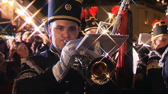 Ein Bergmann spiel bei weihnachtlichem Lichterglanz in seine Trompete