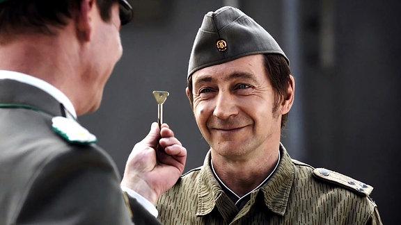 Zwei Männer in Uniform, einer hält einen Schlüssel