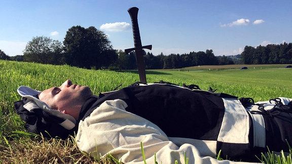 Nachgestellte Szene: Mann in historischer Soldatenuniform liegt mit Dolch in der Brust am Boden