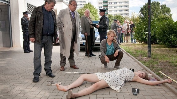 Schmücke (Jaecki Schwarz, 2. von links) und Schneider (Wolfgang Winkler, links) stehen vor der Leiche eines Mädchens, das offensichtlich vom Dach gestürzt is