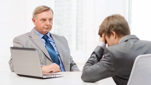 Älterer Mann schaut mit strengem Blick einen jungen Mann an, der seinen Kopf auf die Hand stützt.