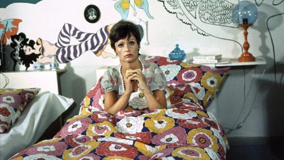 Eine Frau vor einer bunt bemalten und beklebten Wand