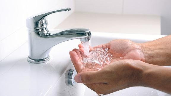 Hände unter einem aus einem Wasserhahn sprudelnden Wasserstrahl