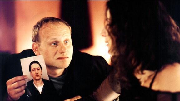 Kain (Bernd Michael Lade) ist auf der Suche nach dem Verdächtigen Martin Kubelka und lernt dabei in einer Bar die schöne Tina kennen (Clelia Sarto)