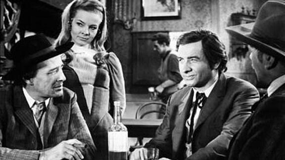 Drei Männer und eine Frau im Saloon. Halbindianer Chris, gespielt von Armin Mueller-Stahl, verdingt sich als Hilfssheriff.