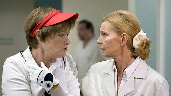 Waltraud Mansfeld (Gertie Honeck, li.) wird mit einer schmerzenden Schulter in die Sachsenklinik eingeliefert. Oberschwester Ingrid (Jutta Kammann, re.) und Prof. Simoni kennen die verwitwete Frau vom Golfplatz.