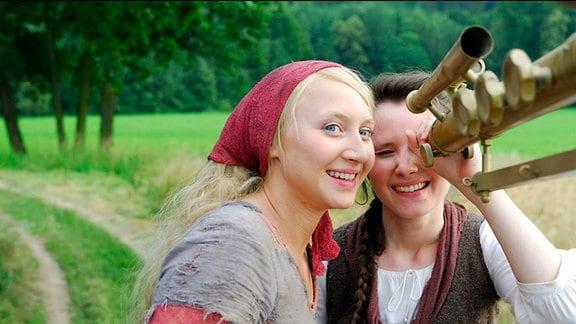 Die kluge Bauerntochter (Anna Maria Mühe) und ihre Freundin die Magd (Sabine Krause) bestaunen das Fernrohr des Königs
