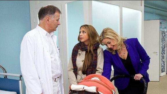 Schwester Arzu spricht zu Dr. Heilmann. Sarah Marquardt herzt Arzus Baby.