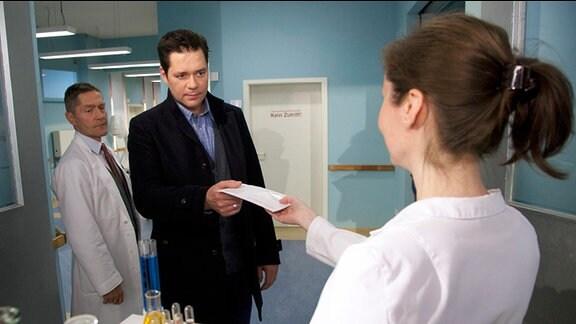 Dr. Brentano erhält von der Labor-Assistentin ein Untersuchungsergebnis. Dr. Kaminski betritt hinter ihm das Zimmer.