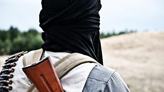 Ein Mann mit einem Gewehr auf dem Rücken guckt in Richtung Horizont.