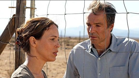 Eine Frau und ein mann stehen sich gegenüber. Zwischen ihnen ist ein grober Drahtzaun. Die Frau blickt zur Seite.