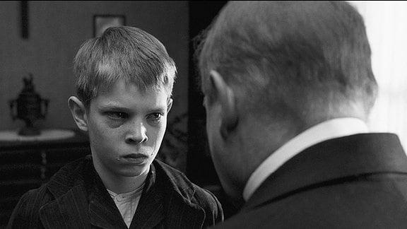 Der bigotte Pastor (Burghart Klaußner) maßregelt seinen Sohn Martin (Leonard Proxauf, li.).