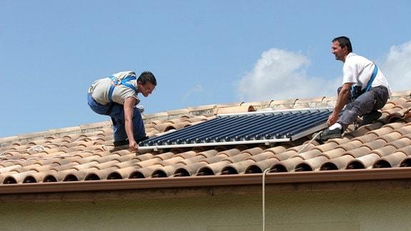 Arbeiter montieren eine Solaranlage auf ein Wohnhaus.