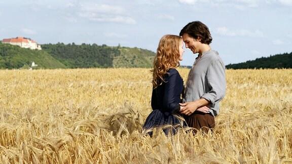Ein junger Mann und eine junge Frau stehen in einem Kornfeld. Sie sehen sich an und umarmen einander.