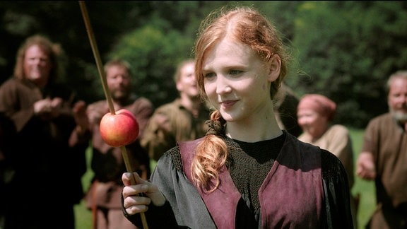 Ein junges Mädchen hält einen Apfel, der von einem Pfeil durchbohrt wurde.