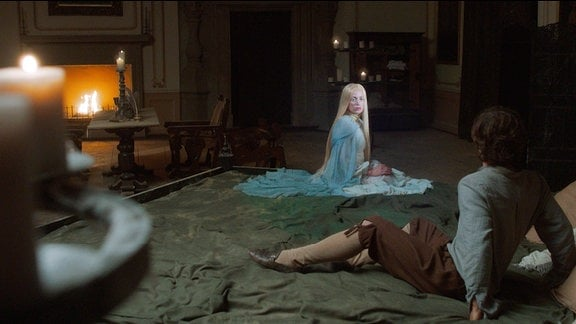 Eine Frau mit blondem Haar und blauem Kleid sitzt bei einem Jungen im Bett, der vor ihr zurückschreckt.