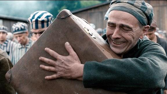Häftling Zacharias Jankowski (Robert Mika) mit dem Koffer, in dem das Kind versteckt ist.