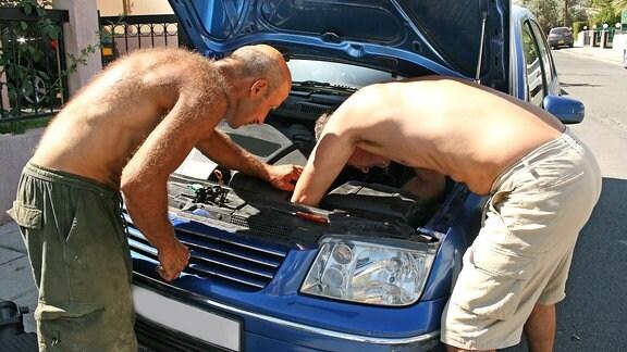 Zwei Männer mit freiem Oberkörper beugen sich über den Motorraum eines blauen Pkws