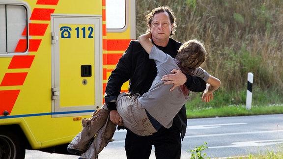 Christian Peintner (Matthias Brandt) ist im Krankenwagen mitgefahren, als sein schwer verletzter Sohn den Notärzten unter den Händen wegstirbt. Er kann nicht fassen, was passiert ist und versucht verzweifelt seinen Sohn Emil (Paul Zerbst) fortzutragen.