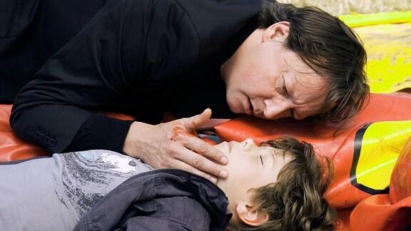 Christian Peintner (Matthias Brandt, oben) kniet schockiert vor seinem schwer verletzten Sohn Emil (Paul Zerbst, unten). Er versucht Erste Hilfe zu leisten, während Hauptkommissarin Eva Saalfeld professionelle Hilfe holt.