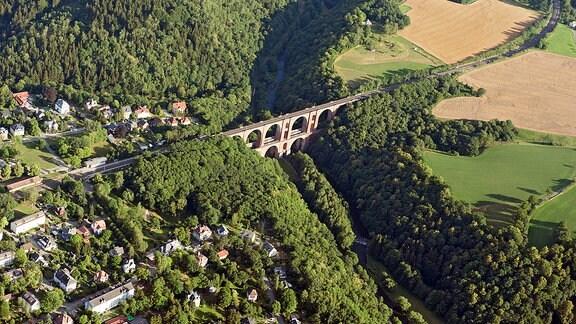 Luftbild einer bewaldeten Landschaft mit ein Dorf und Eisenbahnbrücke.