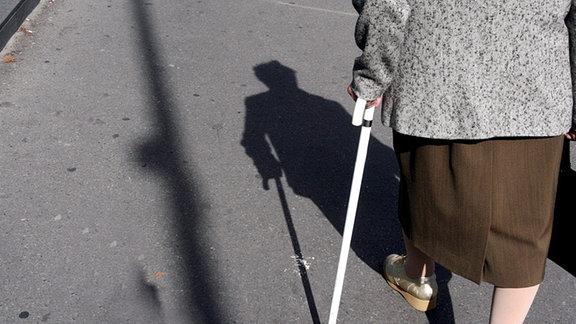 Ein Rentnerin geht am Stock