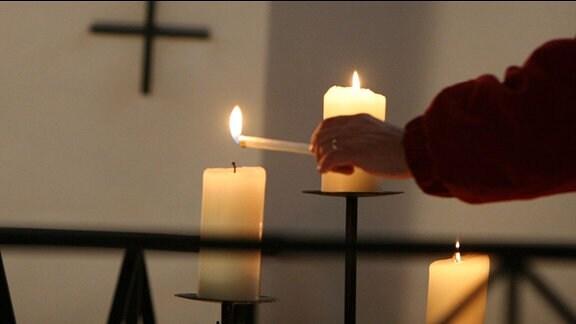 Kerze wird in einer Kirche angezündet