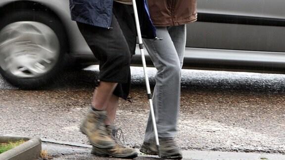 Ein Sehbehinderter mit Stock wird geführt