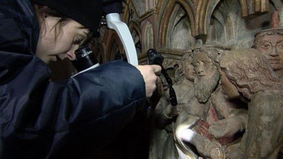 Wissenschaftlerin mikroskopiert am Westlettner des Naumburger Doms