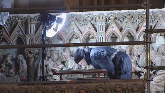 Eine Wissenschaftlerin prüft eine Bauzeichnung im Naumburger Dom