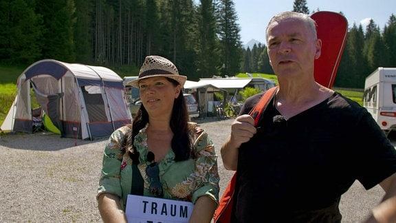 Frau mit Schild und Mann mit Gitarre auf Campingplatz