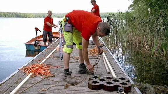 Camper beteiten eine Plattform für ein Seefeuerwerk vor.