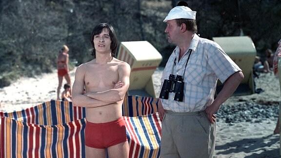 Zwei Männer stehen nebeneinander, einer in Badehose, der andere mit einem Fernglas um den Hals