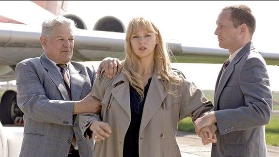 Sara Bender wird am Flugzeug von zwei Männern festgehalten und von ihren Kindern getrennt.
