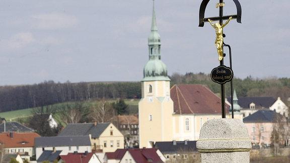 Das Dorf Crostwitz bei Kamenz mit einem Jesuskreuz und den Blick auf die Dorfmitte und die Pfarrkirche.