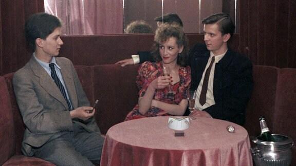 Drei Personen sitzen an einem Tisch mit rosafarbener Tischdecke. Ein Mann hat seinen Arm und die Frau gelegt, ein weiterer Mann sitzt daneben