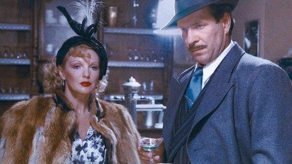Eine Frau und ein Mann, stehen an einer Bar, der Mann hat ein Glas vor sich.
