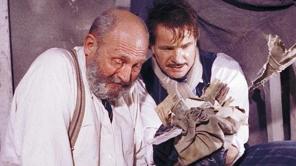 Zwei Männer, einer hält ein Stoffbündel in der Hand, in dem sich Geld befindet