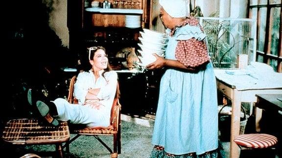 Eine junge Frau, in einem Stuhl sitzend, unterhält sich mit einer älteren Haushälterin, die mehrere Teller trägt.