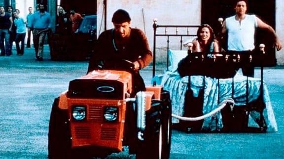 Ein Mann zieht, auf einem Traktor sitzend, ein Bett samt junger Frau durch ein Dorf. Die umstehenden Leute schauen verwundert.